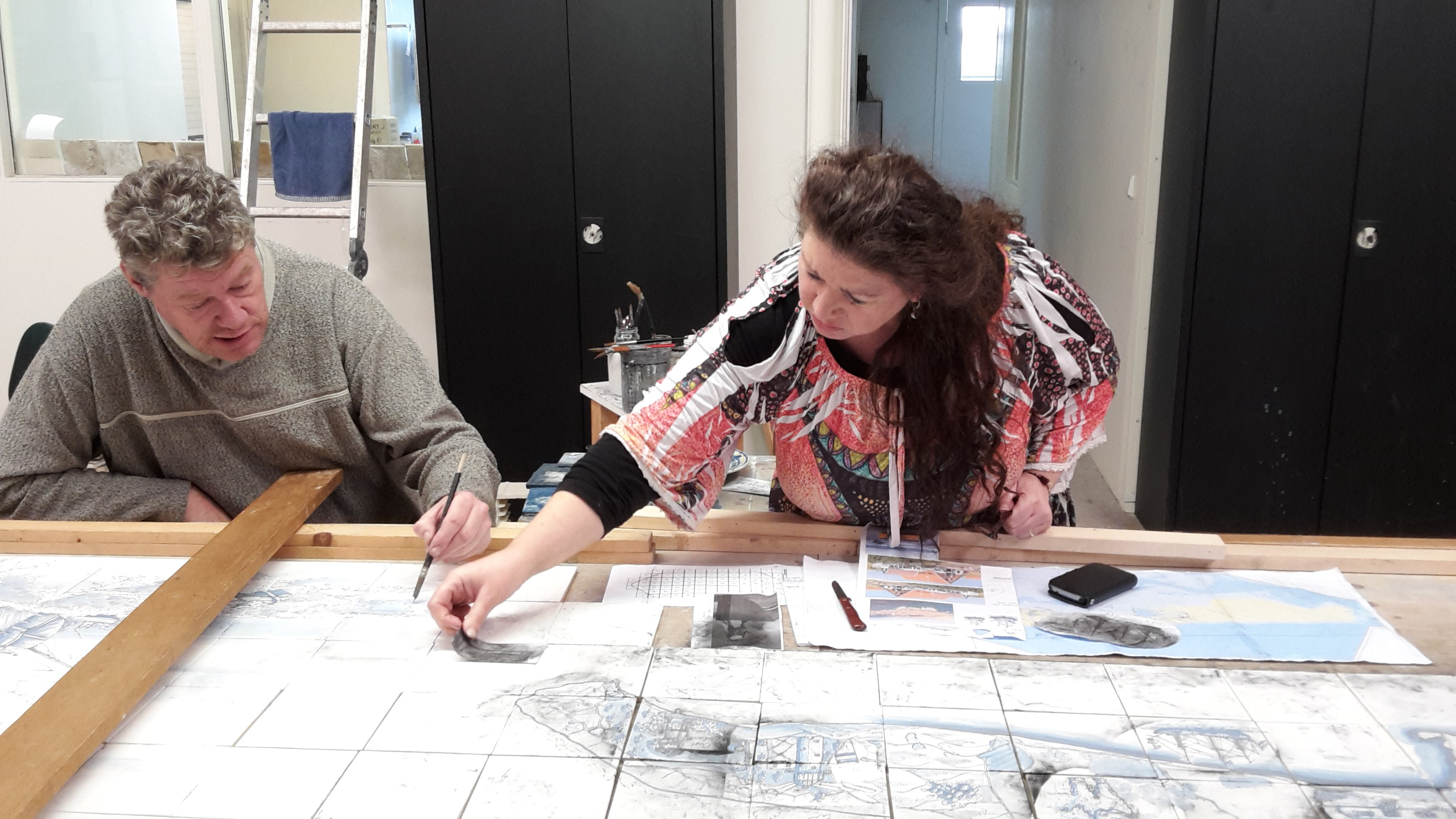 Harm Posthumus en Lucia Bazzano werken aan één van de tegeltableaus